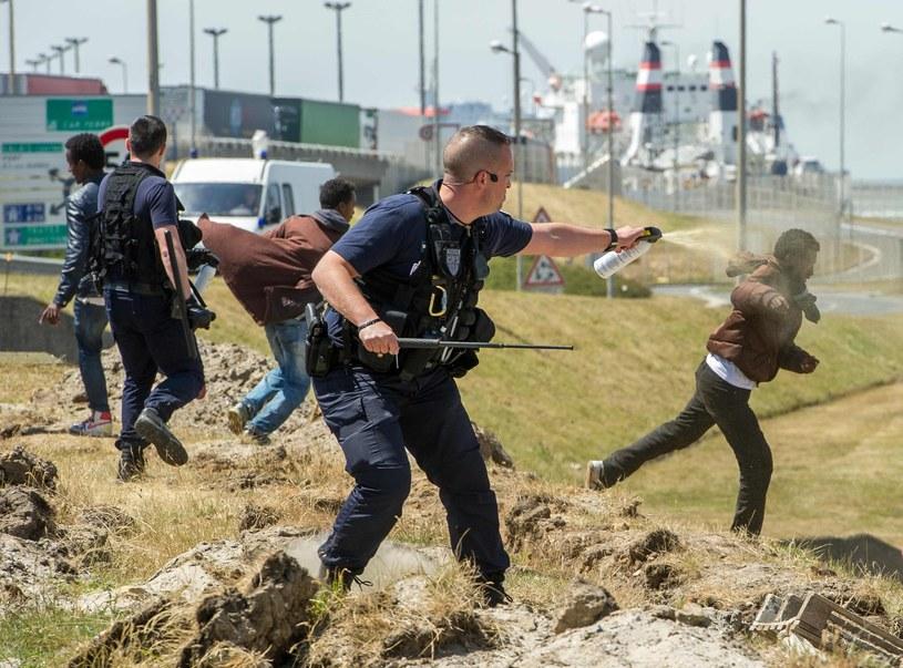 Francuscy policjanci próbują uspokoić migrantów w Calais /AFP
