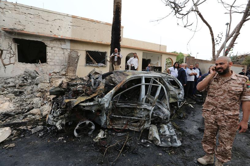Funkcjonariusz libijskich sił bezpieczeństwa na tle samochodu pułapki /MAHMUD TURKIA  /AFP