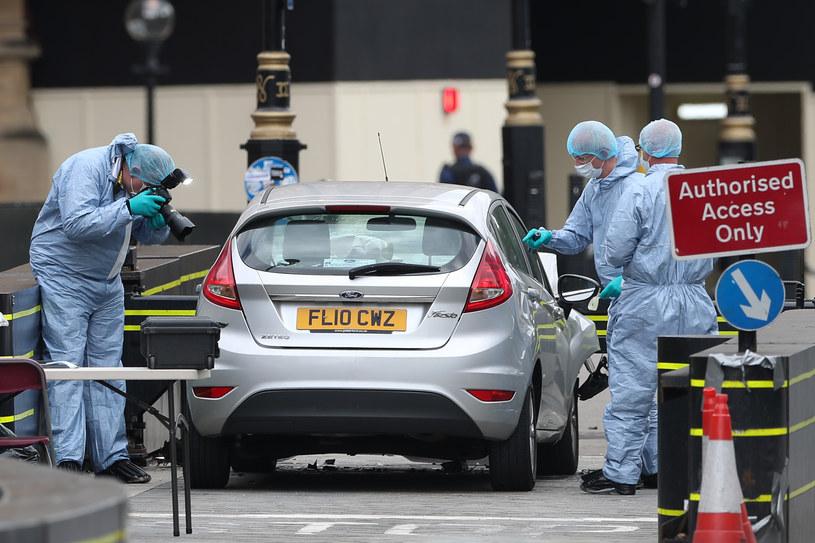 Funkcjonariusze pracujący wokół srebrnego samochodu Ford Fiesta, który 14 sierpnia wjechał w barierkę bezpieczeństwa przed brytyjskim parlamentem /DANIEL LEAL-OLIVAS /AFP