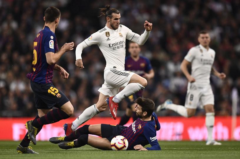 Gareth Bale przeskakuje Gerarda Pique /AFP