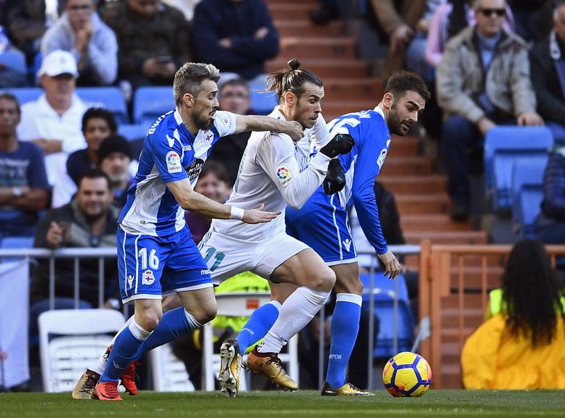 Garteh Bale (w środku) walczy o piłkę z Luisinho i Adrianem Lopezem /AFP