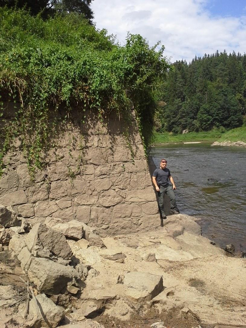 Gdy woda opadnie okazuje się potężną prawie trzy metrową kamienną podstawą, oddzielającą zapewne wcześniej koryto dla kół wodnych. /Odkrywca