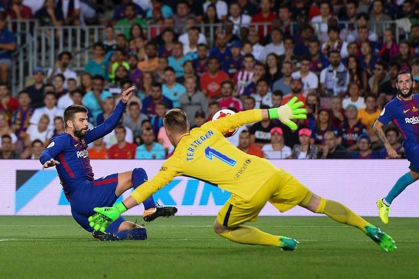 Gerard Pique (L) strzela samobójczego gola w meczu z Realem Madryt /AFP