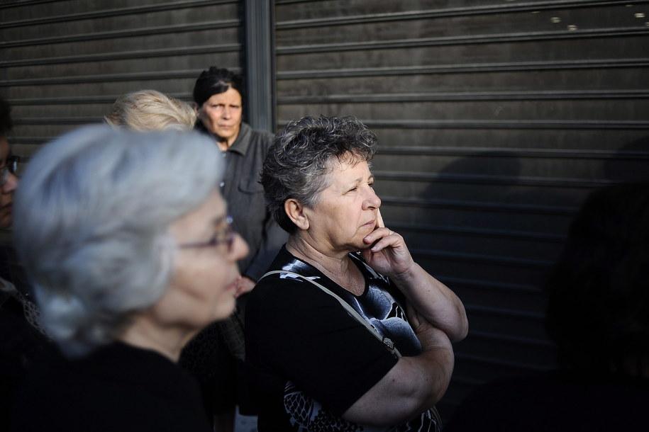 Greccy emeryci, którzy nie posiadają kart do bankomatów, czekają w kolejce przed bankiem w Peristeri pod Atenami, by wypłacić pieniądze z kont. Pozostali Grecy mogą korzystać wyłącznie z bankomatów /FOTIS PLEGAS G. /PAP/EPA