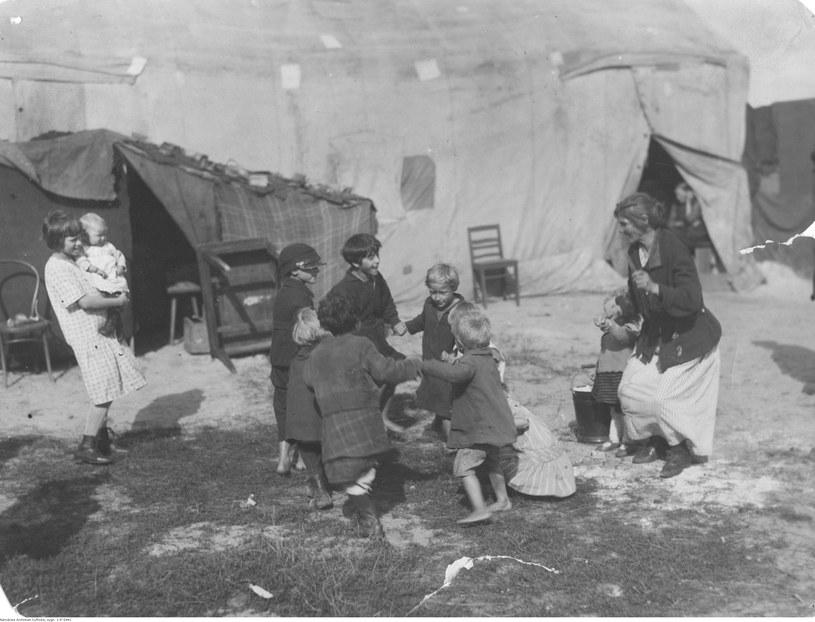Grupa dzieci z bezrobotnych rodzin podczas zabawy przed prowizorycznymi namiotami mieszkalnymi na terenie osiedla dla bezdomnych w pobliżu Dworca Gdańskiego na Żoliborzu /Z archiwum Narodowego Archiwum Cyfrowego