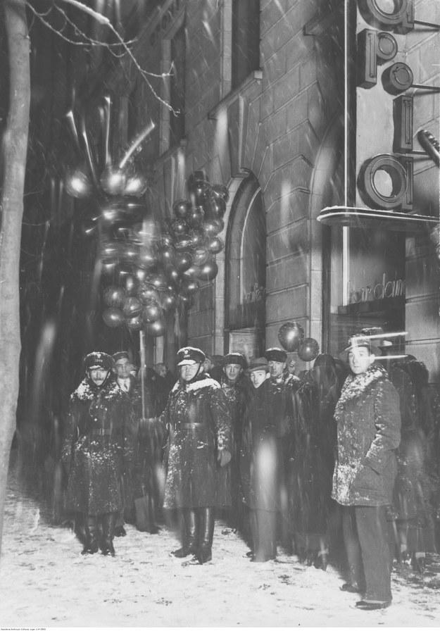 """Grupa osób przed lokalem """"Adria"""". Na pierwszym planie widoczni policjanci, na drugim sprzedawca balonów /Z archiwum Narodowego Archiwum Cyfrowego"""