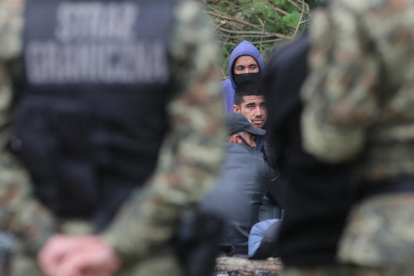 Grupa uchodźców i straż graniczna w pobliżu miejscowości Usnarz Górny / Artur Reszko    /PAP