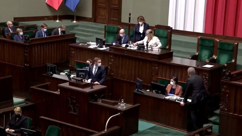 Grzegorz Braun bez maseczki pochywa się nad pracownicą Sejmu /