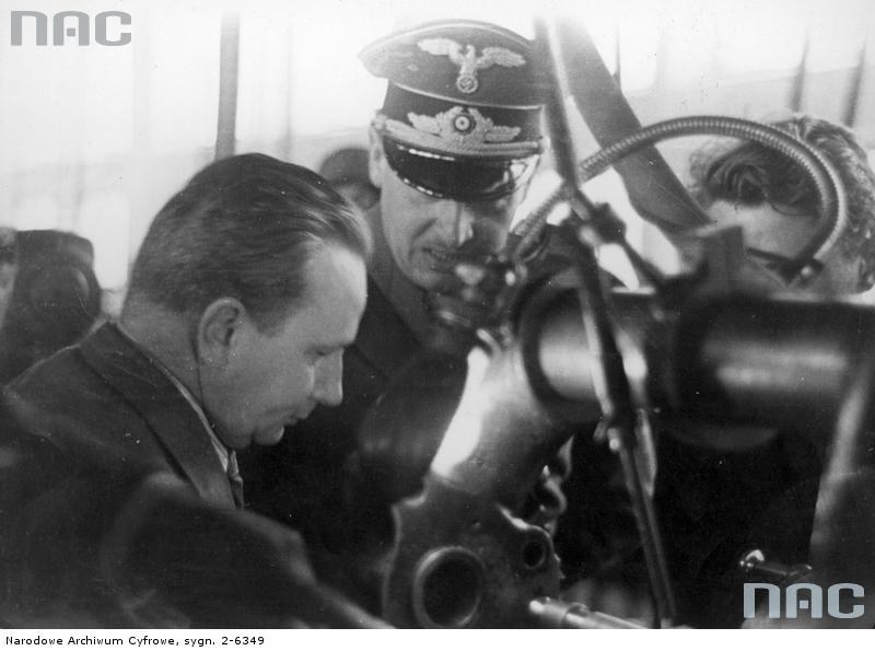 Gubernator Hans Frank podczas zwiedzania radomskiej Fabryki Broni ogląda maszynę produkcyjną /Ze zbiorów Narodowego Archiwum Cyfrowego