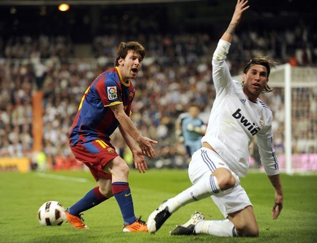 Gwiazdor Barcelony Leo Messi (z lewej) w pojedynku z Sergio Ramosem z Realu Madryt /AFP