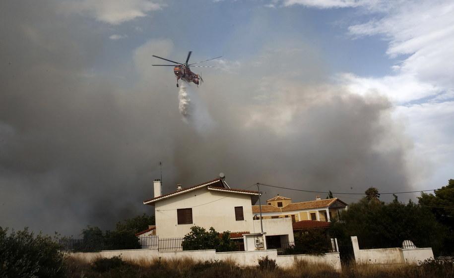 Helikopter zrzuca wodę na dom na północnych przedmieściach Aten /ALEXANDROS VLACHOS /PAP/EPA