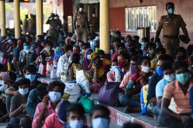 Hinduscy pracownicy, migrujący po kraju w poszukiwaniu lepszej pracy, siedzą stłoczeni na peronie w oczekiwaniu na specjalny pociąg /ARUN SANKAR/Arun SANKAR /AFP