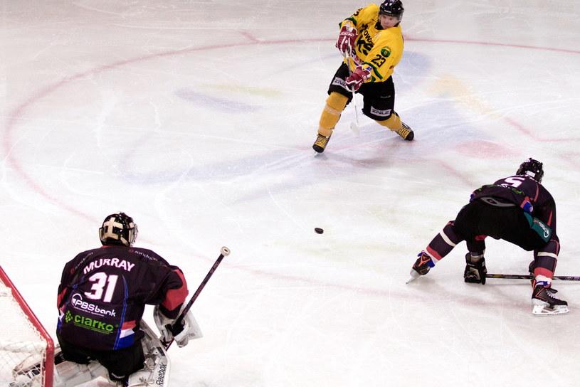 Hokeista HC GKS Katowice Adam Jaskólski (C) strzela na bramkę Johna Murray'a (L) z Ciarko PBS Bank Sanok /Andrzej Grygiel /PAP