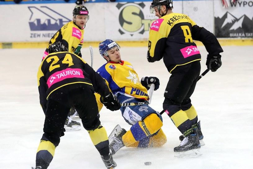 Hokeista TatrySki Podhala Nowy Targ Kacper Guzik (C) oraz Martin Cakajik (L) i Patryk Krężołek (P) z Tauronu KH GKS Katowice / Grzegorz Momot    /PAP