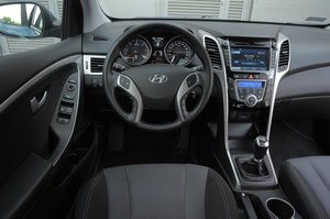 Hyundai i30 Wagon 1.6 GDI Style: dobre materiały i spasowanie, choć nie każdy polubi niebieskie podświetlenie. Przyciski i przełączniki rozplanowano logicznie. Dużo miejsca na drobne rzeczy. Przeszkadzają szerokie słupki A. /Motor