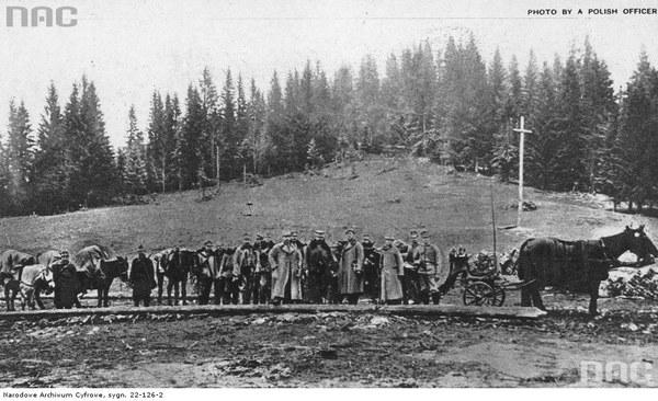 II Brygada Legionów podczas walk w Karpatach. Oddział legionistów. W tle krzyż postawiony przez polskich żołnierzy na granicy Galicji z Węgrami na przełęczy Pantyrowej, 1914