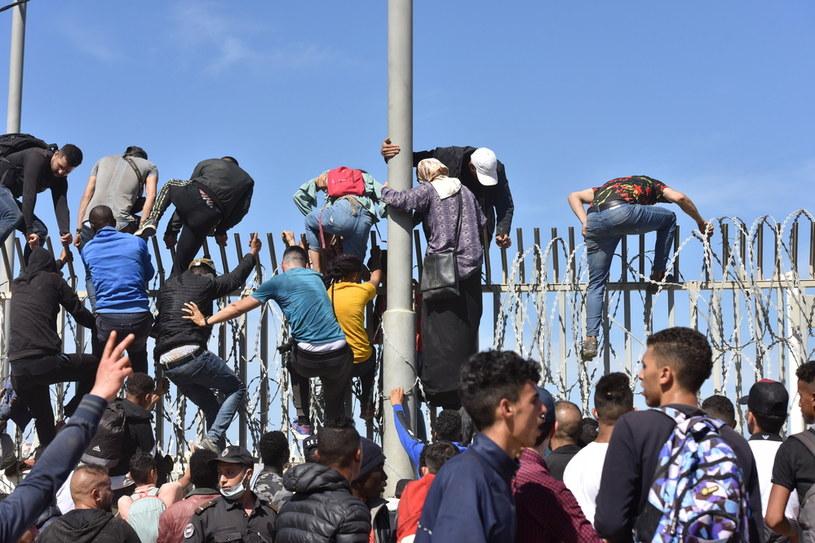 Imigranci z Maroka pokonują zasieki w mieście Fnideq, by dostać się do hiszpańskiej enklawy Ceuta. /PAP/EPA/JALAL MORCHIDI /PAP/EPA
