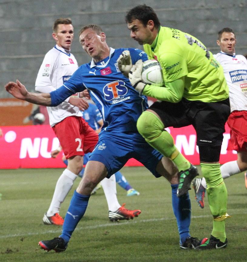 Interweniujący bramkarz Podbeskidzia Ladislav Rybansky (P) chwyta piłkę uprzedzając atakującego Bartosza Ślusarskiego (L) z Lecha Poznań /PAP