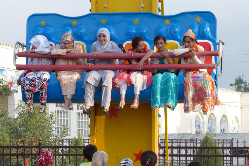 """Istarafszan, Tadżykistan. Wesołe miasteczko jest chyba w każdym postsowieckim mieście. Azja Środkowa niczym się pod tym względem nie różni od innych regionów dawnego ZSRR. Zwane z rosyjska """"atrakcjony"""" są głównym miejscem towarzyskich i rodzinnych weekendowych spotkań. Na zdjęciu dziewczęta na placu zabaw położonym w centrum Istarafszanu. /Styl.pl"""