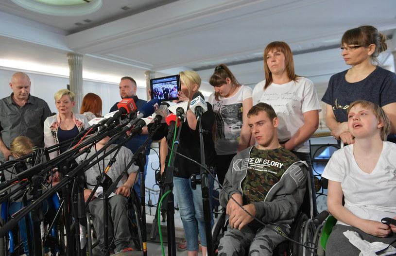 Iwona Hartwich (C) oraz niepełnosprawni i ich opiekunowie podczas konferencji prasowej w Sejmie / Marcin Obara  /PAP