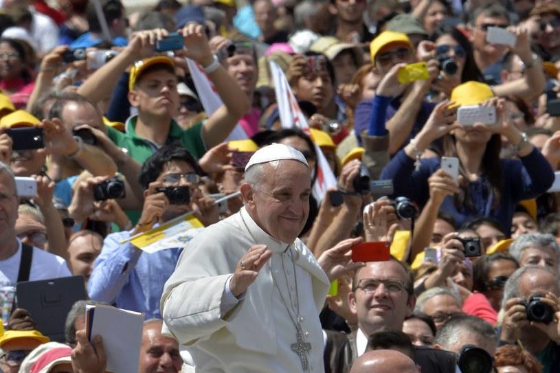 Jadąc w papamobile Franciszek nie tylko pozdrawia i błogosławi, lecz także łapie rzucane mu prezenty. /AFP