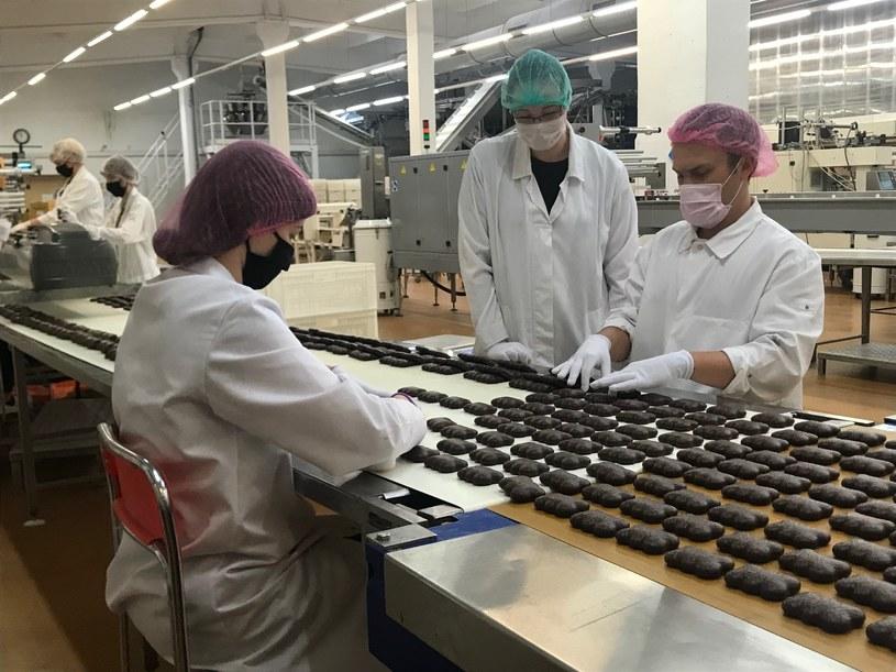 Jakub Kopczyński, dyrektor marketingu, pełniąc rolę stażysty pracuje przy taśmie produkcyjnej w fabryce pierników /