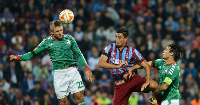 Jakub Rzeźniczak (główkuje) i Ivica Vrdoljak (kapitan Legii) powstrzymują Oscara Cardozo z Trabzonsporu /PAP/EPA