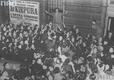 Jan Kiepura podczas przed paryską operą otoczony tłumem wielbicieli. Na ścianie budynku widoczny plakat reklamujący występy artysty