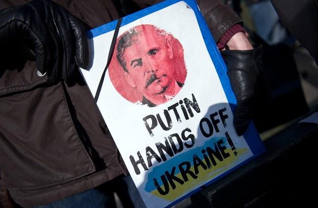 """Jeden z demonstrantów trzyma plakat z napisem: """"Putin, łapy precz od Ukrainy"""" /DANIEL NAUPOLD /PAP/EPA"""