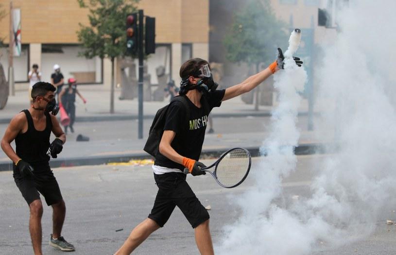 Jeden z protestujących na ulicach Bejrutu - przy pomocy rakiety - odbija kanister z gazem łzawiącym /AFP