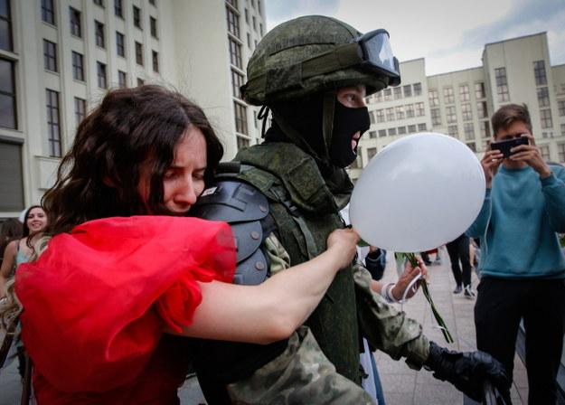 Jedna z protestujących kobiet przytula żołnierza /TATYANA ZENKOVICH  /PAP/EPA
