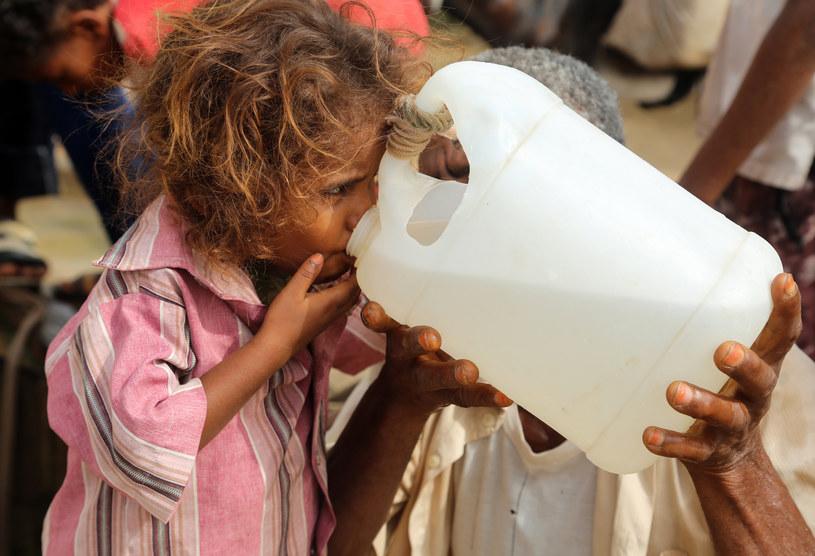 Jemeńska dziewczynka pije wodę ze studni w ubogiej wiosce na obrzeżach miasta Al-Hudajda /Abdo HYDER /AFP