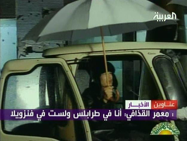 Kadafi został pokazany z parasolem w otwartych drzwiach samochodu /AFP