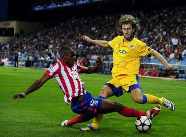 Kamil Kosowski (z prawej, z lewej Luis Perea z Atletico Madryt) w APOEL-u spotkał Moustaphę Bangurę. /AFP