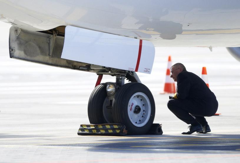 Kapitan samolotu ogląda koło z uszkodzonym amortyzatorem /Adam Warżawa /PAP
