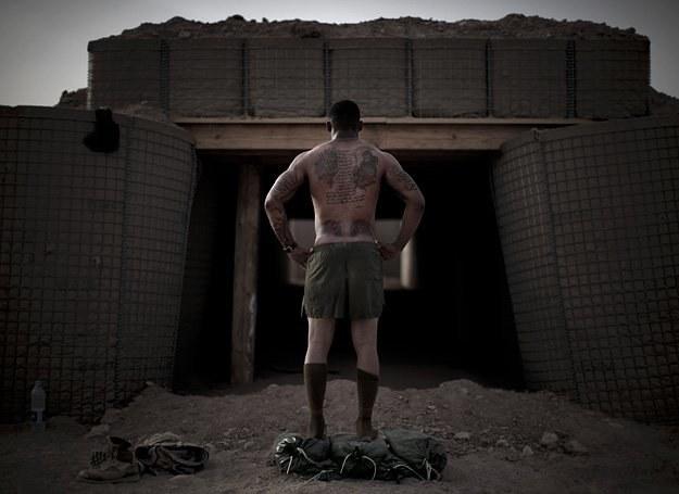 Kapral Jones Kendall pokazuje tatuaże na swoim ciele przed bunkrem w Mardży, na południu Afganistanu /AFP