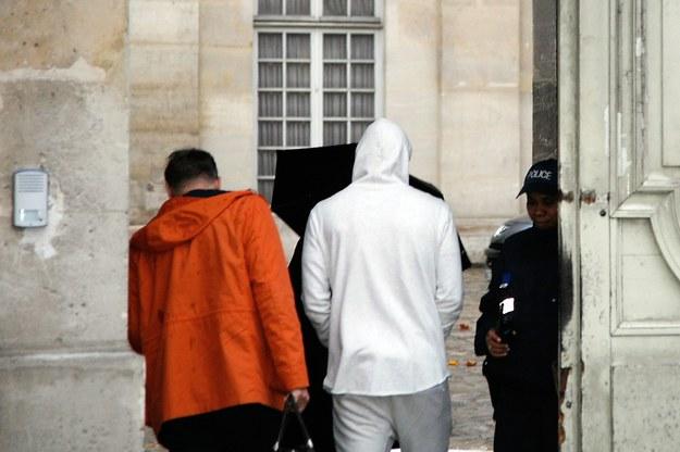 Karim Benzema (w kapturze) doprowadzany na komisariat /AFP