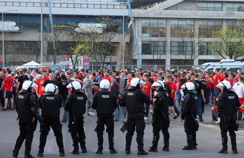Kibice Widzewa pod stadionem w otoczeniu policjantów /Stanisław Rozpędzik /PAP