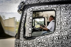Kierowca tira, podczas jazdy, z tabletem w ręku
