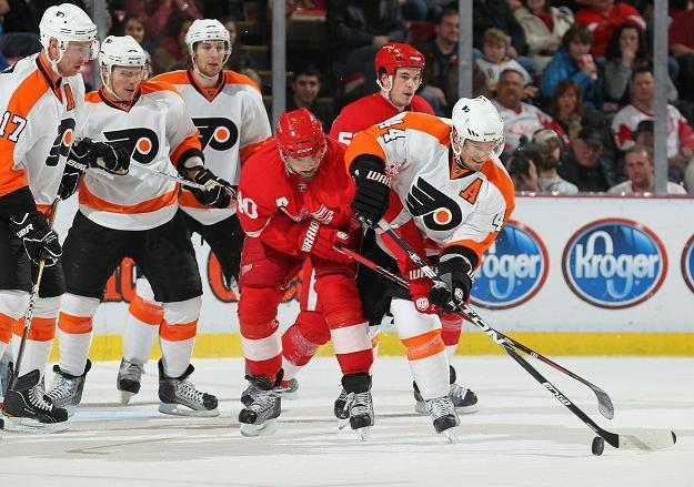 Kimmo Timonen z Philadelphia Flyers walczy o krążek z Henrikiem Zetterbergiem z Detroit Red Wings /AFP
