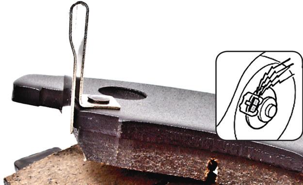 Klocek z czujnikiem akustycznym. Po zużyciu się warstwy ciernej, blaszka zaczyna dotykać tarczy i głośno piszczy. /Motor