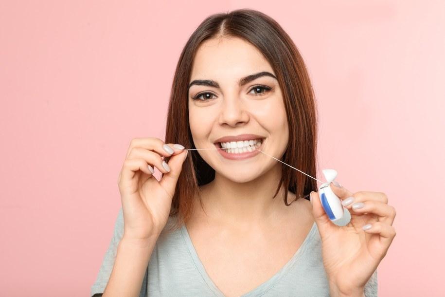 """""""Kluczowym jest przełamanie mitu, że nitkowanie zębów jest drugorzędne. Szczotkując zęby, nie docieramy do wszystkich zakamarków, więc czyścimy je połowicznie"""" - wyjaśnia stomatolog /adobestock /"""
