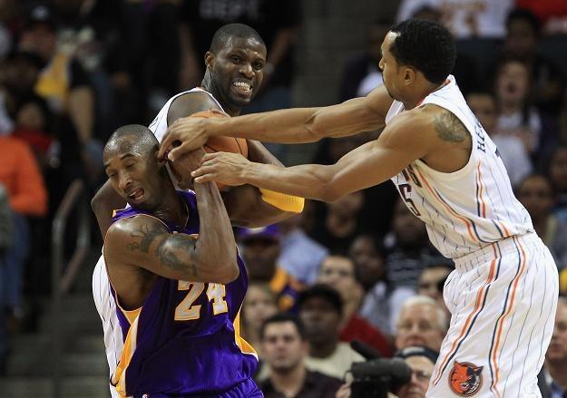 Kobe Bryant (z lewej) walczy o piłkę z Nazrem Mohamedem i Geraldem Hendersonem z Charlotte Bobcats /AFP