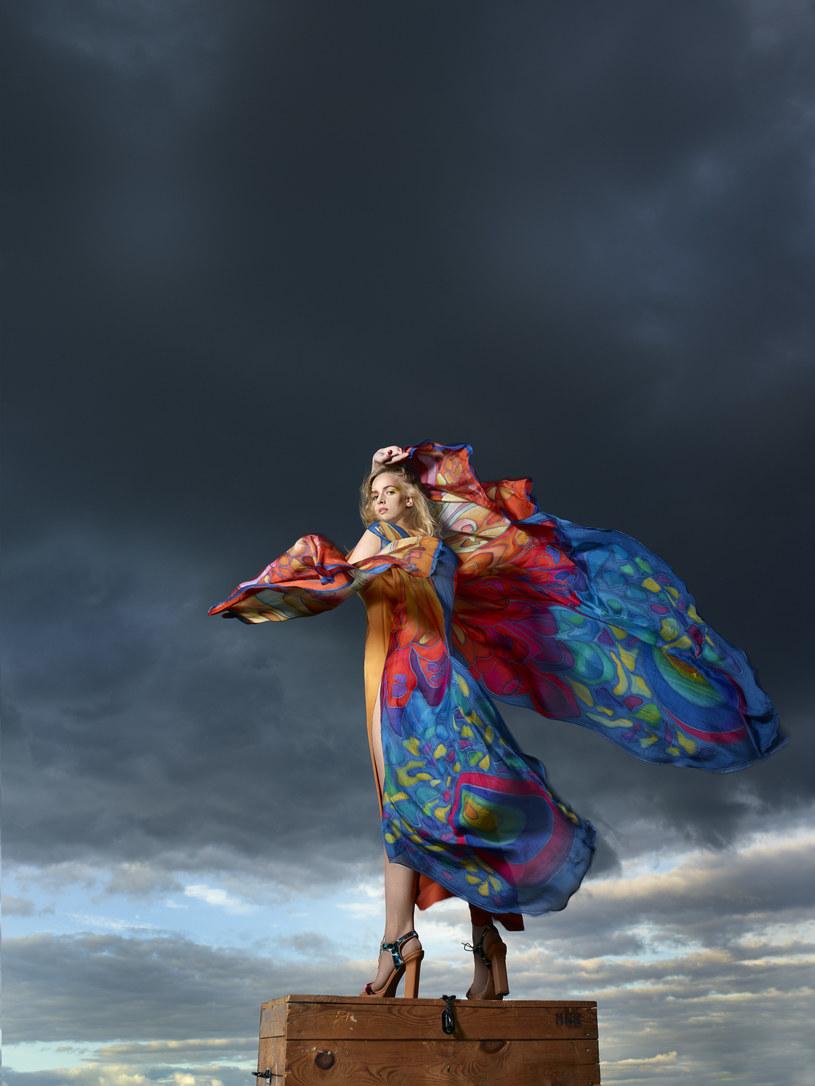 """Kobieta-motyl. Współpraca Kaliny Paroll i Zakładów Jedwabiu Naturalnego w Milanówku zaowocowała jedną z najbardziej niezwykłych kreacji """"Mody Polskiej"""" z lat siedemdziesiątych. Kobieta-motyl nosi wąską sukienkę podkreślającą wysmukłość niby owadziego tułowia. Peleryna w ruchu przypomina rozpostarte w locie bajecznie kolorowe skrzydła, 1979, wł. MNK/buty współczesne. Fot. Pracownia Fotograficzna MNK /materiały prasowe"""