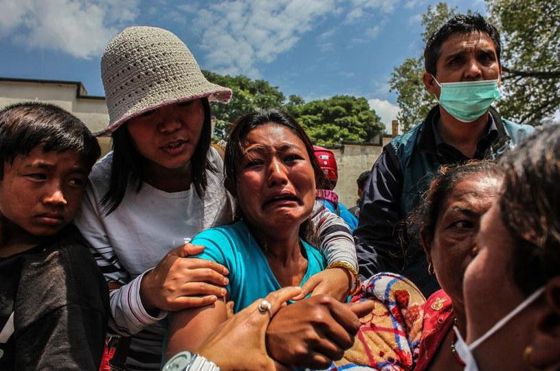 Kobieta płacze, ponieważ w zawalonym budynku znajdowali się jej ojciec i brat /NurPhoto/REX Shutterstock /East News