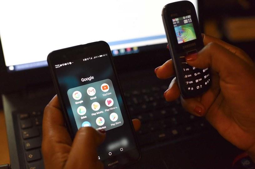Kobieta używająca dwóch telefonów przed ekranem laptopa /ISSOUF SANOGO /AFP