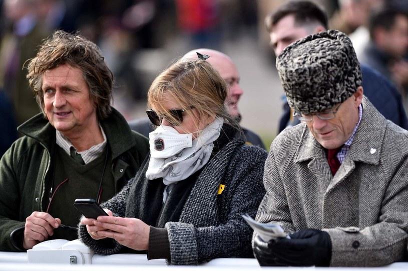 Kobieta w masce podczas marcowych wyścigów konnych w Cheltenham /GLYN KIRK /AFP
