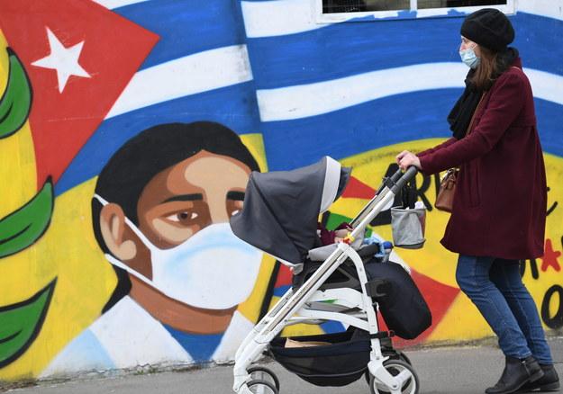 Kobieta z wózkiem przy muralu w Mediolanie /DANIEL DAL ZENNARO  /PAP/EPA