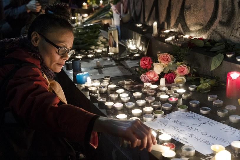 Kobieta zapala świecę na Placu Republiki w Paryżu /PAP/EPA