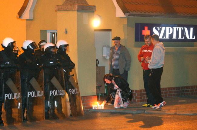 Kobieta zapala znicz przed szpitalem w Knurowie /Andrzej Grygiel /PAP